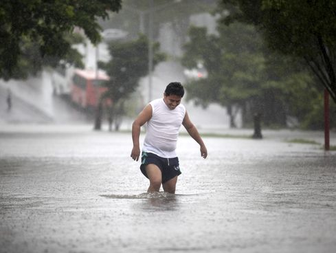 A man walks through a flooded street during heavy rains caused by Tropical Storm Ingrid in the Gulf port city of Veracruz, Mexico, Friday Sept. 13., 2013. / Felix Marquez, AP
