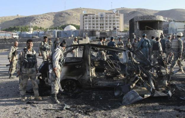 Afghan security forces inspect a damaged car, which was used during a suicide bomb attack, outside the U.S. consulate in Herat province on Sept. 13, 2013. Reuters